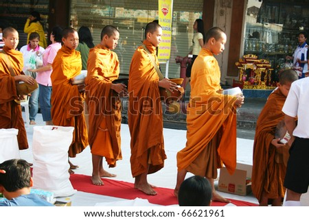 BANGKOK - DECEMBER 5: Buddhist monks walk collecting alms in the morning on the king's birthday on December 5, 2010 in Bangkok, Thailand.