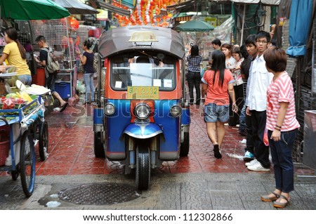 BANGKOK - FEB 4: A three-wheeled tuk tuk taxi drives along a busy road in Chinatown on Feb 4, 2012 in Bangkok, Thailand. Tuk tuks can be hired from as little as $1 or B30 a fare for short trips. - stock photo