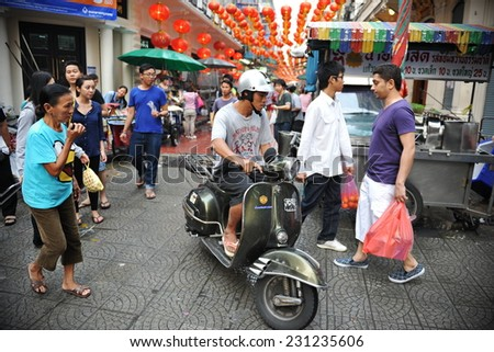 BANGKOK - FEB 4: People make their way along a busy market street in Chinatown on Feb 4, 2012 in Bangkok, Thailand. Chinese began settling in the Thai capital's Chinatown circa 1800s. - stock photo