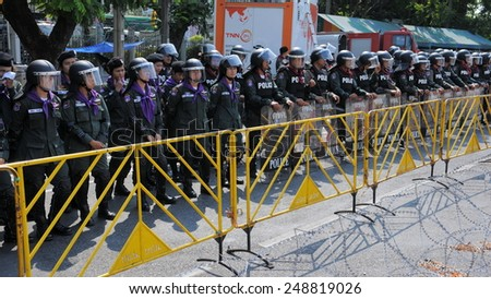 BANGKOK - FEB 11: Riot police stand guard at Government House during a protest on Feb 7, 2011 in Bangkok, Thailand. Royalist Yellow Shirt protesters gathered in opposition to upcoming elections. - stock photo