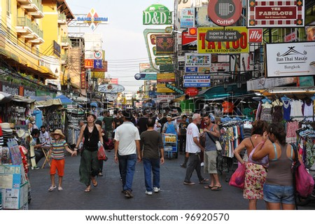 BANGKOK - FEB 25: Tourists walk along backpacker haven Kaosan Road as officials warn visas on arrival may be rolled back in the wake of recent terrorism incidents on Feb 25, 2012 in Bangkok, Thailand. - stock photo