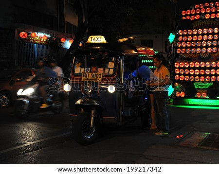 BANGKOK - FEB 9: Unidentified people stop a tuk tuk taxi on a street at night on Feb 9, 2013 in Bangkok, Thailand. The ubiquitous tuk tuk can be hired for as little as $1 or B30 for short trips.