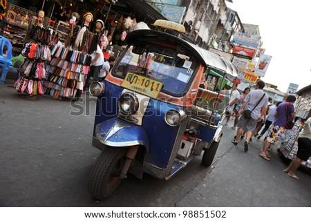 BANGKOK - FEBRUARY 25: A three-wheeled tuk tuk taxi drives along Khao San Road on February 25, 2012 in Bangkok, Thailand. Tuk tuks can be hired from as little as $1 or B30 a fare for shop trips. - stock photo