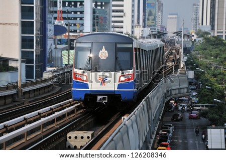 BANGKOK - JAN 25: A BTS Skytrain on elevated rails in Ratchathewi district on Jan 25, 2013 in Bangkok, Thailand. Each train of the mass transport rail network can carry over 1,000 passengers. - stock photo