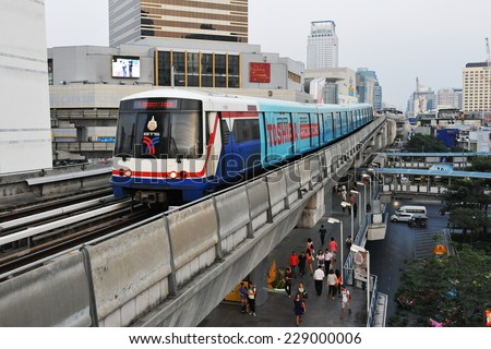BANGKOK - JAN 16: A BTS Skytrain on elevated rails runs above a city centre road on Jan 16, 2013 in Bangkok, Thailand. Each train of the mass transport rail network can carry over 1,000 passengers. - stock photo