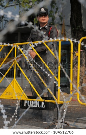 BANGKOK - JAN 25: A policeman guards a barricade outside Government House, the site of during daily anti-goverment protests and bomb alerts, on Jan 25, 2011 in Bangkok, Thailand. - stock photo