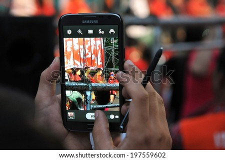 BANGKOK - JAN 29: A protester uses a phablet device to capture a city centre red-shirt rally on Jan 29, 2013 in Bangkok, Thailand. Protesters gathered to demand political prisoners be freed. - stock photo