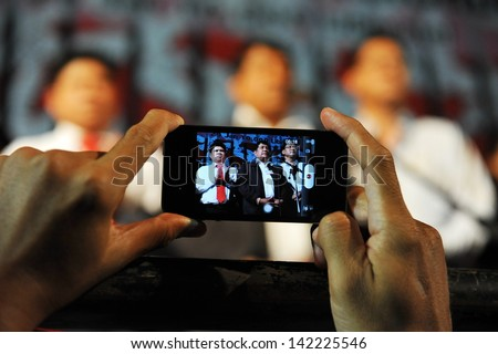 BANGKOK - JAN 29: A protester uses a smartphone to photograph a Red Shirt rally on the Royal Plaza on Jan 29, 2013 in Bangkok, Thailand. Protesters gathered to demand political prisoners be freed. - stock photo
