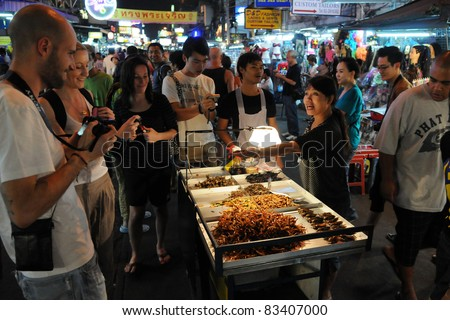 BANGKOK - JAN 30: A street vendor sells fried cockroaches and other insects to tourists on Khao San Road on Jan 30, 2011 in Bangkok, Thailand. There is 16,000 registered street vendors in Bangkok. - stock photo