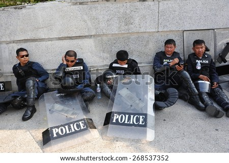 BANGKOK - JAN 27: Riot police rest during an anti government rally at a city centre military facility on Jan 27, 2014 in Bangkok, Thailand. The Thai capital has seen months of political instability. - stock photo