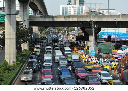 BANGKOK - JAN 25: Traffic nears gridlock on a busy road in the city centre on Jan 25, 2013 in Bangkok, Thailand. Annually an estimated 150,000 new cars join the heavily congested roads of Bangkok. - stock photo