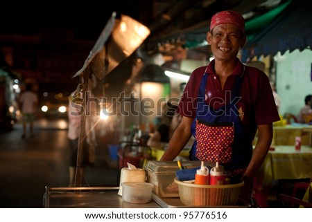 BANGKOK - JANUARY 12. An unidentified man cooking on Khao San Road on January 12, 2012 in Bangkok, Thailand. Street cooking is a tradition and ubiquitous in Thailand. - stock photo