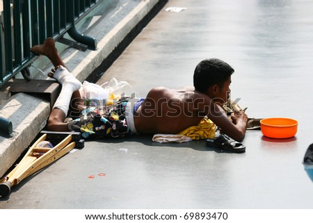 BANGKOK - JANUARY 10: Thai crippled man begs for money on a bridge on January 10, 2010 in Bangkok, Thailand. - stock photo