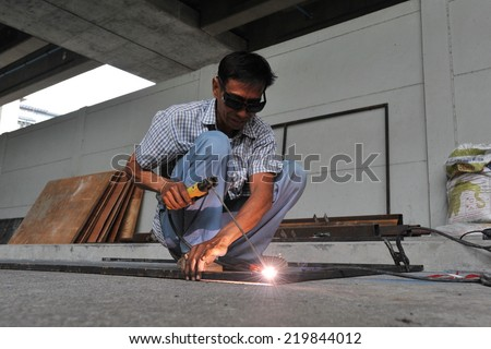 BANGKOK - JUL 8: An unidentified labourer welds metal on a building site on Jul 8, 2013 in Bangkok, Thailand. The Thai capital is undergoing a construction boom. - stock photo