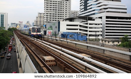 BANGKOK- JULY 07: BTS Skytrain runs on elevated rails above Phaholyothin Road on July 07, 2012 in Bangkok, Thailand. Train can carry over 1,000 passengers to 32 stations around Bangkok and outskirts. - stock photo
