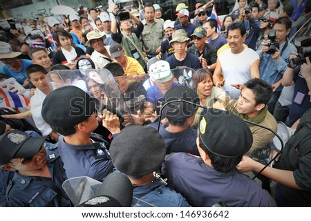 BANGKOK - JULY 21: Protesters scuffle with riot police during an anti-government rally on July 21, 2013 in Bangkok, Thailand. The protesters are calling for the government to be overthrown. - stock photo