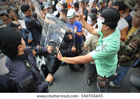 BANGKOK - JULY 21: Protesters scuffle with riot police during an anti-government rally on July 21, 2013 in Bangkok, Thailand. The protesters are calling for the government to be overthrown.