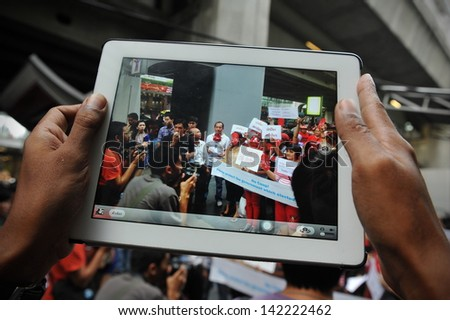 BANGKOK - JUN 2: A protester uses a tablet computer to capture a Red Shirt rally in Bangkok's shopping area on Jun 2, 2013 in Bangkok, Thailand. Protesters rallied to show support to the government. - stock photo