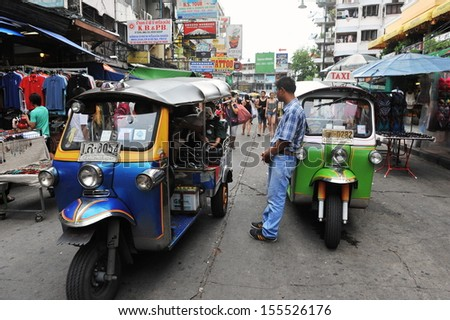 BANGKOK - JUN 5: A three-wheeled tuk tuk taxi transports passengers along Khao San Road on Jun 5, 2013 in Bangkok, Thailand. Tuk tuks can be hired from as little as $1 or B30 a fare for shop trips. - stock photo