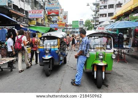 BANGKOK - JUN 5: A three-wheeled tuk tuk taxi transports passengers on Khao San Road on Jun 5, 2013 in Bangkok, Thailand. Tuk tuks can be hired from as little as $1 or B30 a fare for shop trips. - stock photo