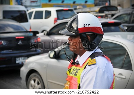 BANGKOK - JUN 15: An unidentified traffic police officer works on a busy road on Jun 15, 2011 in Bangkok, Thailand. Annually an estimated 150,000 new cars join the heavily congested roads of Bangkok. - stock photo