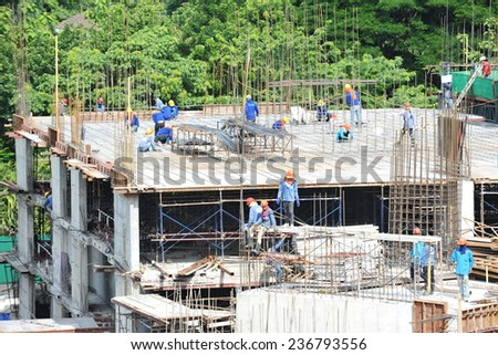 BANGKOK - JUN 24: Labourers work on a high rise city centre construction site on Jun 24, 2012 in Bangkok, Thailand. The Thai capital is undergoing a construction boom. - stock photo