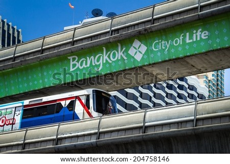 BANGKOK - JUNE 9: A BTS Skytrain on elevated rails in Sathorn district on June 9, 2014 in Bangkok, Thailand. Each train of the mass transport rail network can carry over 1,000 passengers. - stock photo