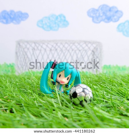 BANGKOK - JUNE 18, 2016 : Miniature of Hatsune Miku (vocaloid girl with turquoise pigtails) is playing soccer on the artificial grass and blur kid crayon colour drawing background. Editorial Used Only - stock photo