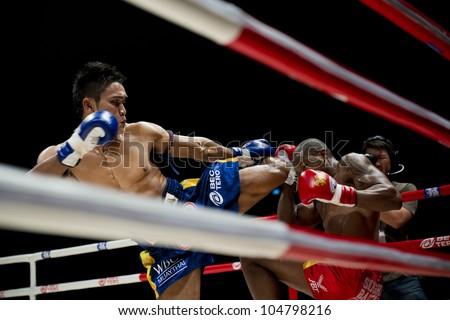 "BANGKOK - JUNE 9: Muay Thai Super Welterweight World Championship - Kem Sitsongpeenong (TH) foot kicking Alejandro Asumu Osa (ES) at ""BATTLE FOR THE BELTS"" event on June 9, 2012 in Bangkok, Thailand - stock photo"