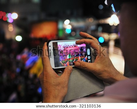 BANGKOK - MAR 19: A passerby uses a smartphone to capture a Thai boxing match on a city centre street on Mar 19, 2013 in Bangkok, Thailand. Thailand has one of the world's highest uses of Istagram. - stock photo