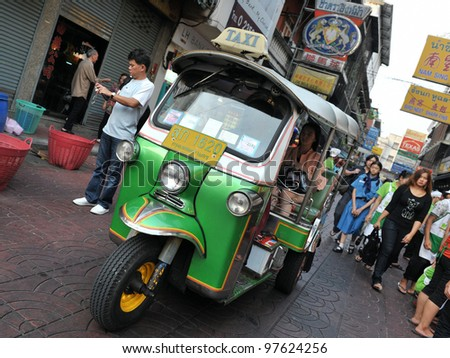 BANGKOK - MARCH 2: A three wheeled  tuk-tuk taxi drives along a road in Chinatown on March 2, 2012 in Bangkok, Thailand. There are an estimated 10,000 tuk-tuks operating in the Thai capital. - stock photo