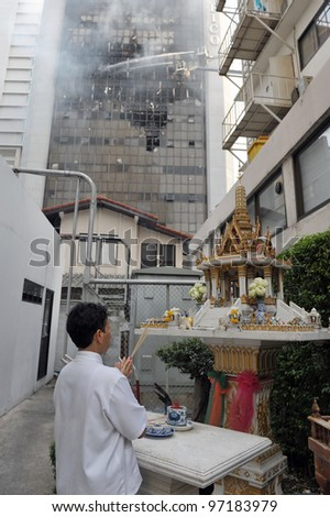 BANGKOK - MARCH 5: An unidentified woman prays at a spirit house as firefighters tackle a blaze at Fico Building on March 5, 2012 in Bangkok, Thailand. - stock photo