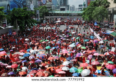 BANGKOK - MAY 19: Red-shirts protest at Ratchaprasong Junction on May 19, 2011 in Bangkok, Thailand. The red-shirts gathered to mark one year since 91 people died in protests in the Thai capital. - stock photo