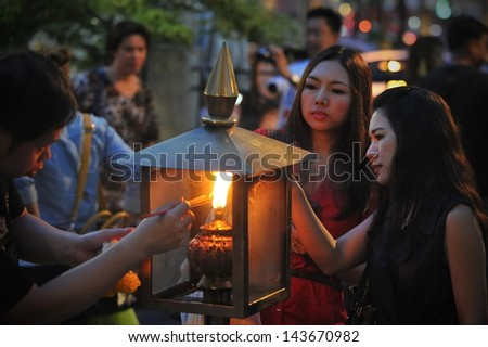 BANGKOK - MAY 24: Temple-goers light incense during a merit making ceremony at the Erawan Shrine on May 24, 2013 in Bangkok, Thailand. The shrine was built in 1956 and has become a popular landmark. - stock photo