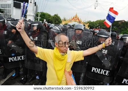 BANGKOK - NOV 24: A nationalist anti-government protesters from Pitak Siam confronts riot police on Makhawan Bridge on Nov 24, 2012 in Bangkok, Thailand.  - stock photo