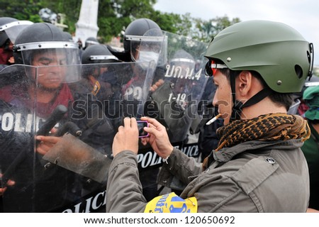 BANGKOK - NOV 24: A protesters uses a smartphone to photograph riot police while participating in an anti-government rally organised by nationalist Pitak Siam on Nov 24, 2012 in Bangkok, Thailand. - stock photo