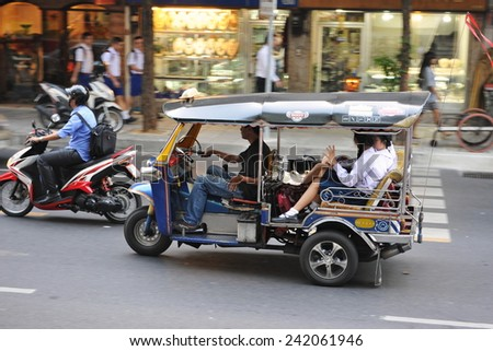 BANGKOK - NOV 5: A tuk tuk taxi transports passengers on a busy Chinatown street on Nov 5, 2012 in Bangkok, Thailand. Tuk tuks in theThai capital can be hired from $1 or B30 a fare for short trips. - stock photo