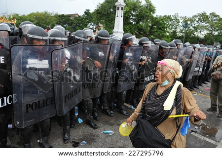 BANGKOK - NOV 24: An anti-government protester confronts riot police during a violent rally on Nov 24, 2012 in Bangkok, Thailand. The protesters call for the government to be overthrown. - stock photo