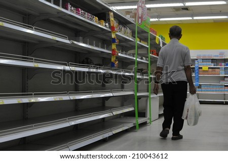 BANGKOK - NOV 3: An unidentified shoppers browses empty shelves in a supermarket on Nov 3, 2011 in Bangkok, Thailand. Many shops are low on goods due to floods preventing deliveries and panic buying. - stock photo
