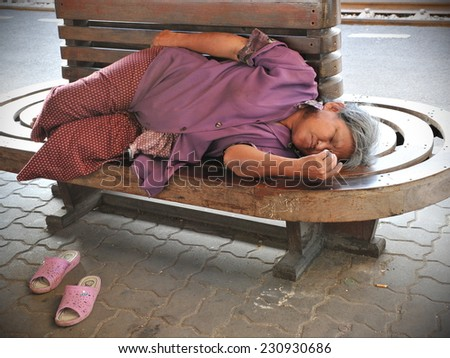 BANGKOK - NOV 18: An unidentified woman sleeps on a street bench on Nov 18, 2011 in Bangkok, Thailand. Thailand's severe flooding has exacerbated homelessness with almost 14 million people displaced.