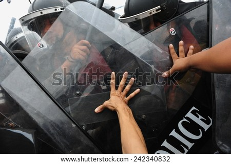 BANGKOK - NOV 24: Anti government protesters push shields of riot police during a violent a large rally on Nov 24, 2012 in Bangkok, Thailand. Protesters call for the government to be overthrown. - stock photo