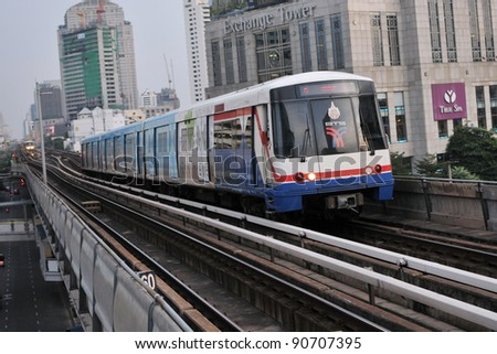 BANGKOK - NOVEMBER 4: A BTS Skytrain on elevated rails above Sukhumvit Road on November 4, 2011 in Bangkok, Thailand. Each train of the mass transport rail network can carry over 1,000 passengers. - stock photo