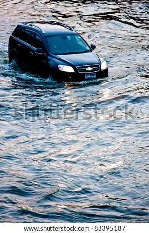 BANGKOK - NOVEMBER 5: A car navigates through the flood on Phahonyothin Road during the worst flooding in Bangkok, Thailand on November 5, 2011. - stock photo