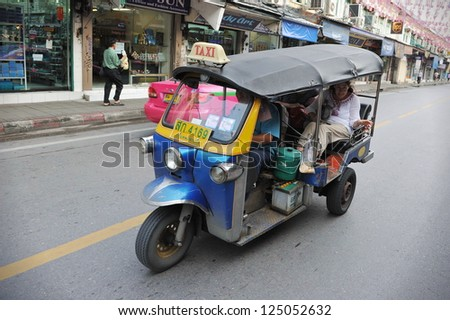 BANGKOK - OCT 31: A tuk tuk taxi transports passengers on a road in the Khao San area on Oct 31, 2012 in Bangkok, Thailand. Tuk tuks can be hired from as little as $1 or B30 a fare for shop trips. - stock photo