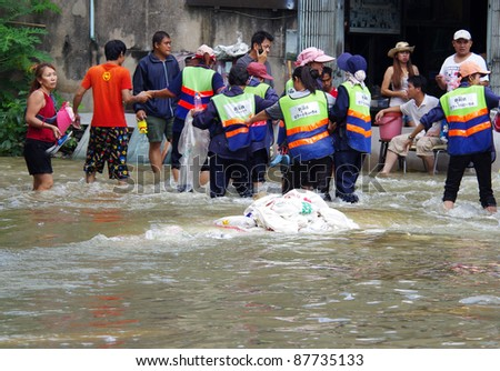BANGKOK - OCT 30: Unidentified residents of Bangkok's  Dusit district make their way through flooded streets after the Chao Phraya River bursts its banks on Oct 30, 2011 in Bangkok, Thailand. - stock photo