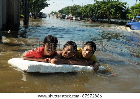 BANGKOK - OCTOBER 28: unidentified children swimming through deep water on a small Foam  during the flooding of October 28, 2011 in Bangkok, Thailand. - stock photo