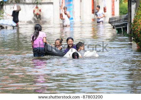 BANGKOK - OCTOBER 29: Unidentified girls swimming at the entrance of Srisudaram temple on west side of Chaopraya river during Thai flood crisis on October 29, 2011 in Bangkok, Thailand.