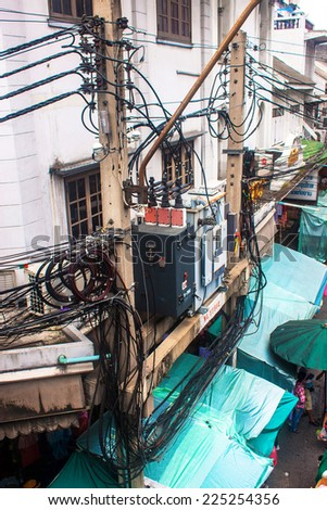 BANGKOK - SEP 6: Mess of wires in Chinatown on Sep 6, 2013 in Bangkok, Thailand. Such chaotic wiring is very common in Bngkok. - stock photo
