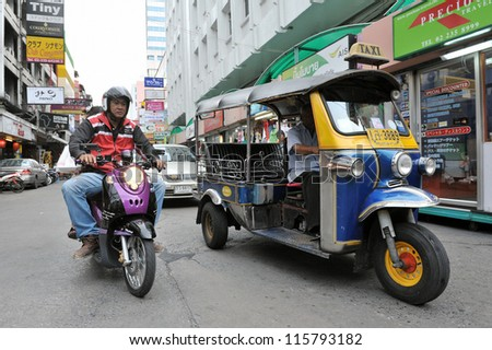 BANGKOK - SEPT 10: A three-wheeled tuk tuk taxi drives along a road in Silom district on Sept 10, 2012 in Bangkok, Thailand. Tuk tuks can be hired from as little as $1 or B30 a fare for shop trips. - stock photo
