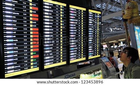 BANGKOK - SEPT 19: An unidentified man looks at the departures board at Suvarnabhumi International Airport on Sept 19, 2012 in Bangkok, Thailand. The airport handles 45 million passengers annually. - stock photo